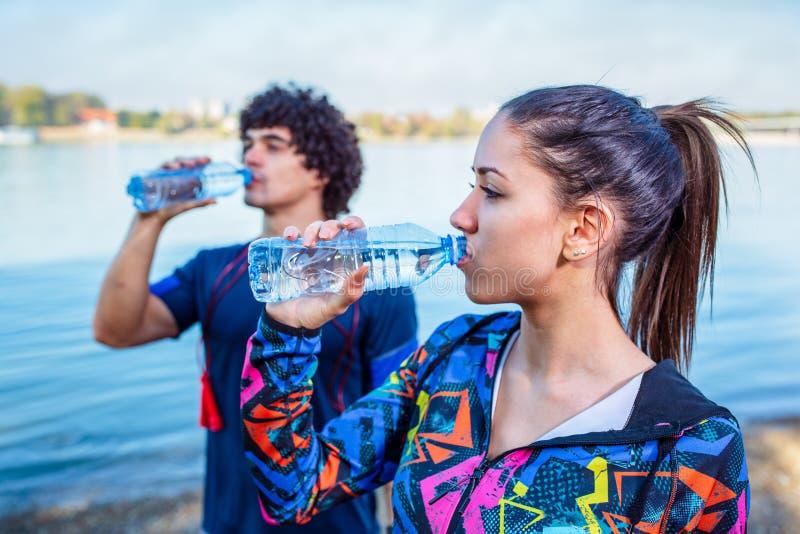 休息,在锻炼妇女喝水重新补充能量后 免版税库存图片