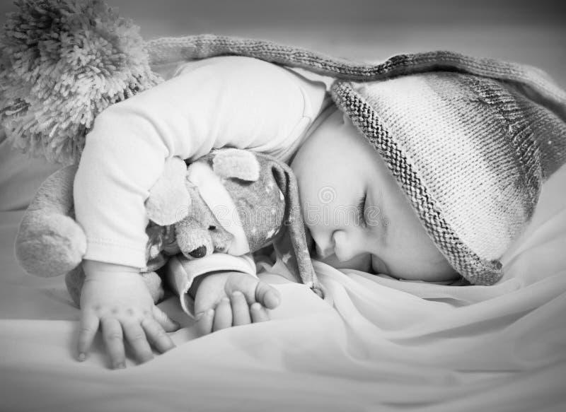 休眠与玩具的女婴 免版税库存图片