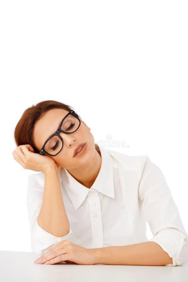 休眠在她的服务台的乏味女实业家 免版税库存照片