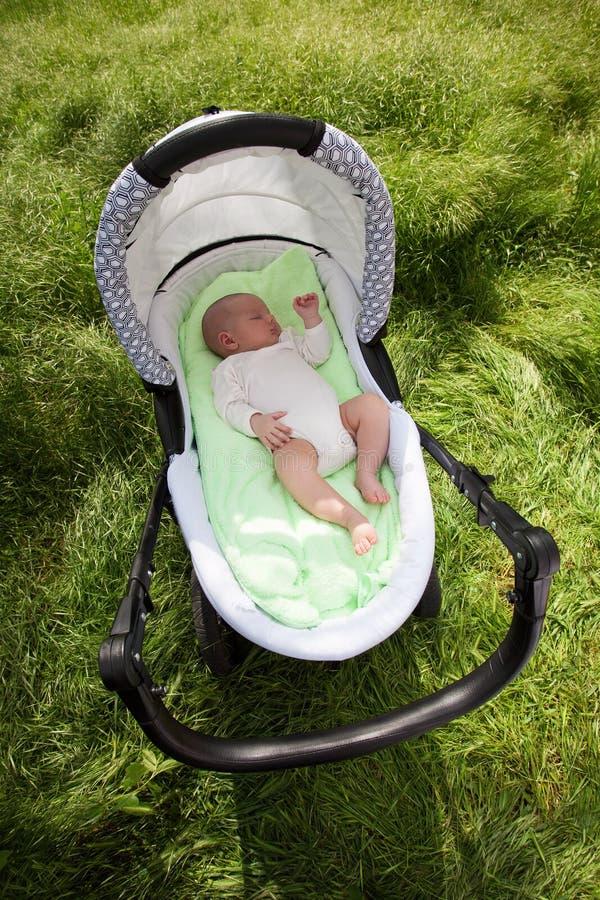 休眠在摇篮车的男婴户外 免版税库存照片