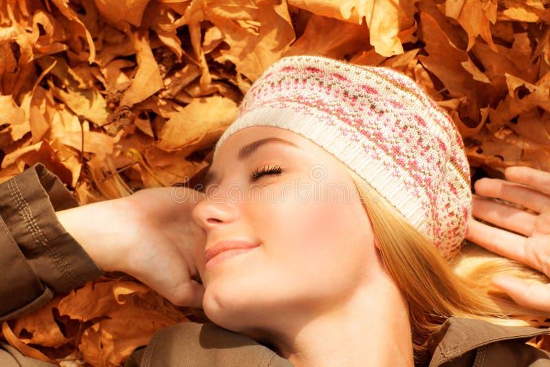 休眠在秋叶的俏丽的妇女 免版税库存照片