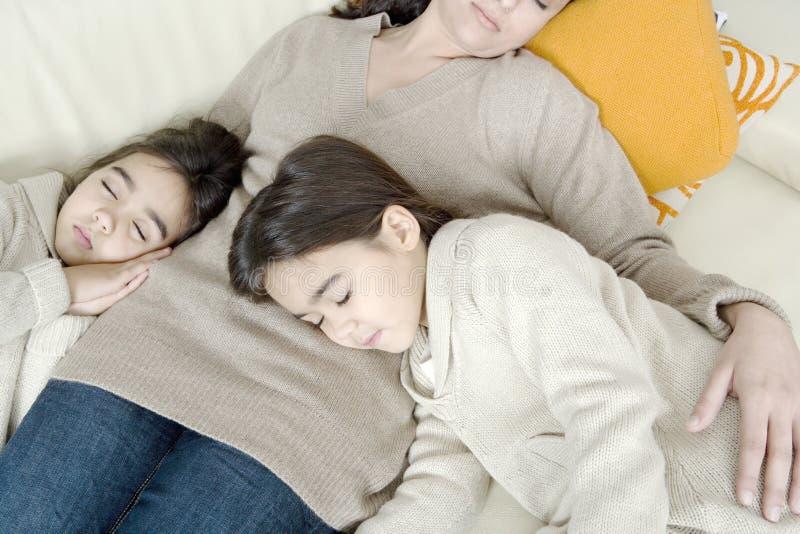 休眠在长沙发的妈咪和女儿 库存图片