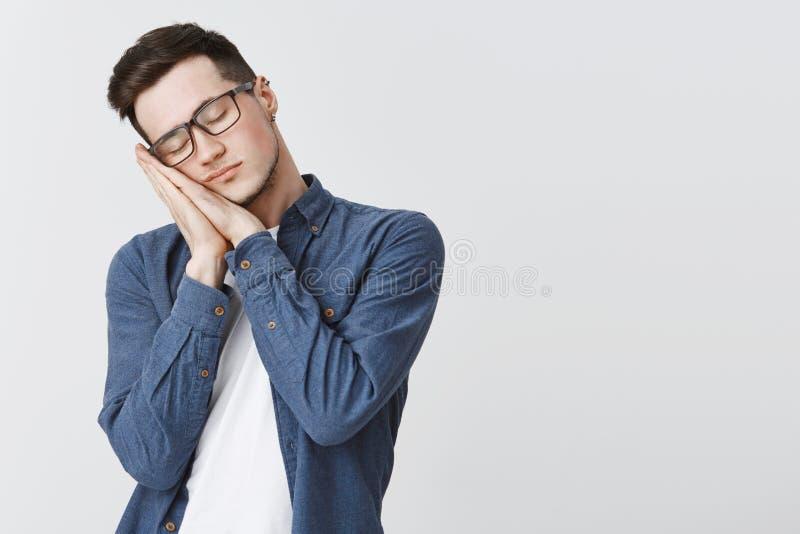 休眠时间 戴被刺穿的站立与闭合的眼睛的耳朵和眼镜的疲乏的可爱的年轻人倾斜在棕榈作为枕头 免版税库存照片