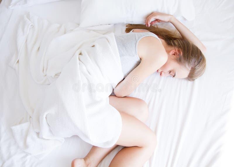休眠 睡觉在床,女性基于上的少妇与枕头的舒适的床在白色卧具在轻的卧室 库存照片