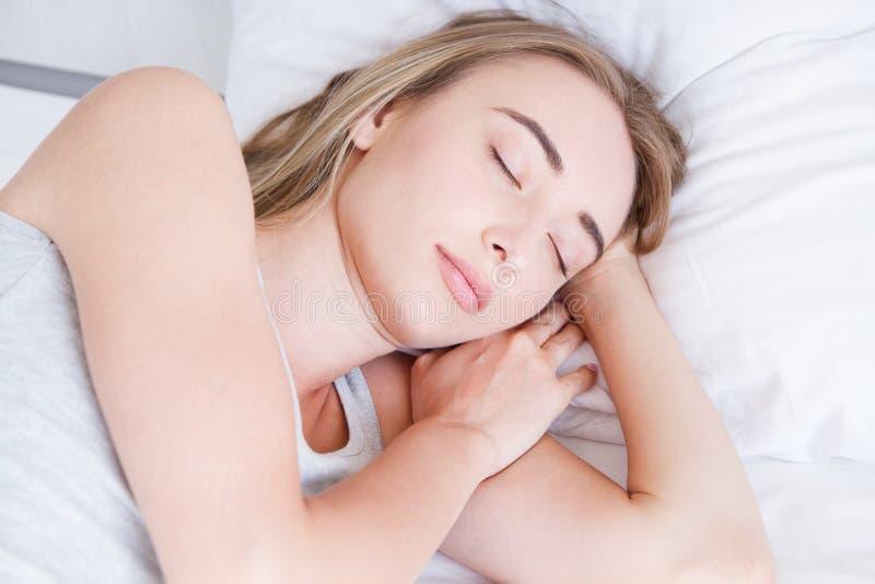 休眠 睡觉在床,画象上的少妇美好女性基于与枕头的舒适的床在白色卧具 库存照片