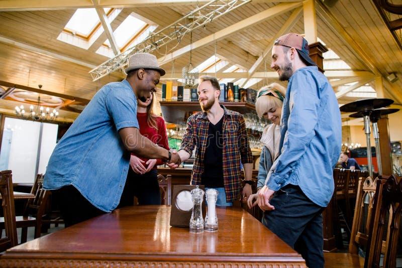 休闲、人们和假日概念-小组五个年轻多种族微笑的朋友开会议在咖啡馆 库存图片