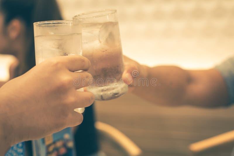休闲、假日,吃,人和食物概念-吃晚餐在餐馆和使饮料叮当响的朋友 免版税库存图片