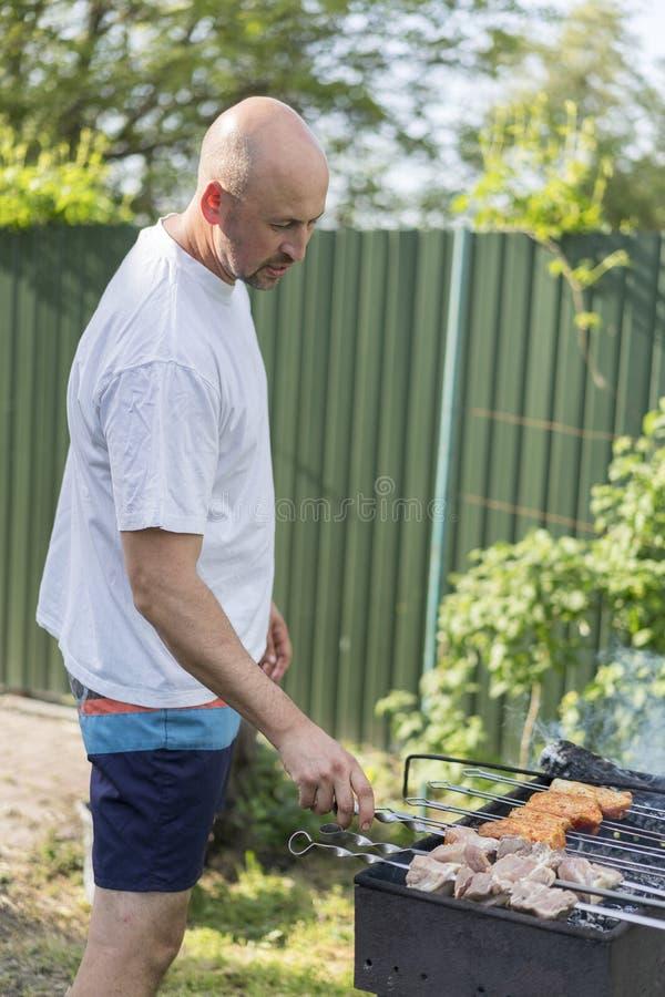 休闲、食物、人们和假日概念-烹调在烤肉格栅的愉快的年轻人肉在室外夏天党 免版税图库摄影