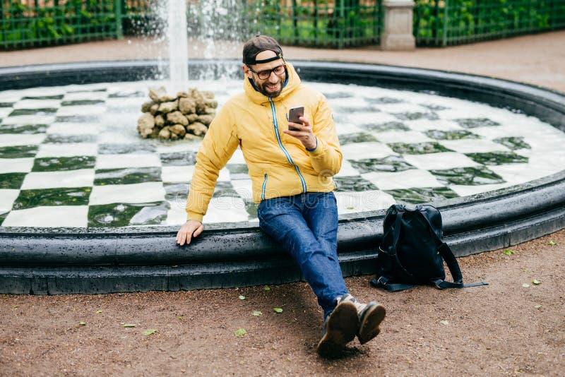 休闲和业余时间概念 无忧无虑的人画象有胡子的在留给他的背包在喷泉附近我们的便衣穿戴了 免版税库存图片