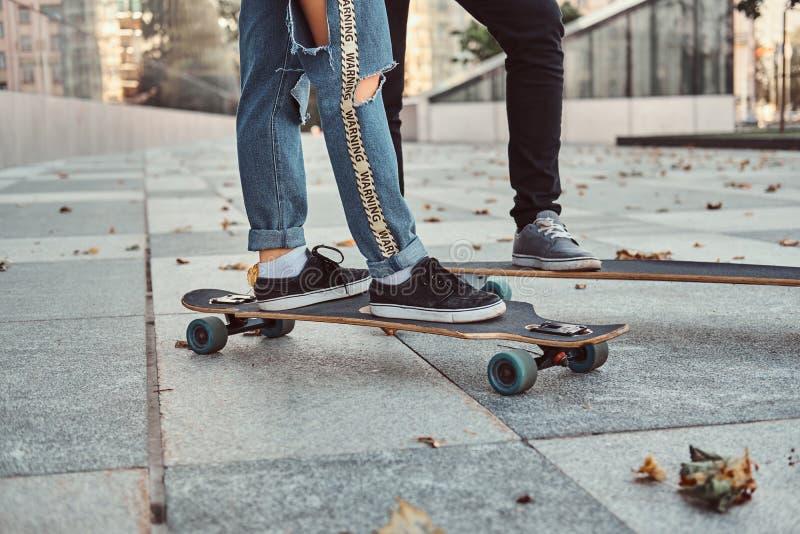 休闲和体育概念-一时髦穿戴的青少年的加上的特写镜头照片在街道上的滑板 免版税库存图片