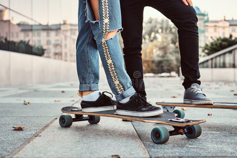 休闲和体育概念-一时髦穿戴的青少年的加上的特写镜头照片在街道上的滑板 图库摄影