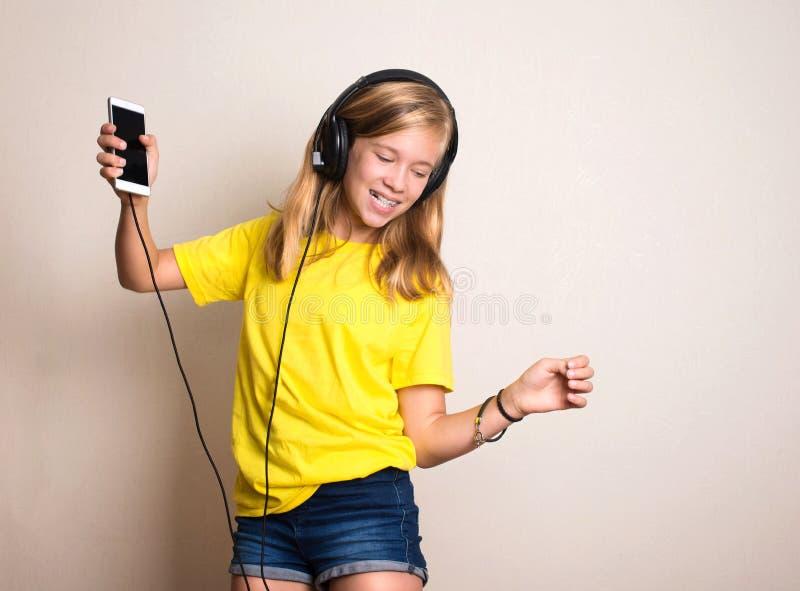休闲概念 耳机锂的愉快的前青少年或十几岁的女孩 库存图片