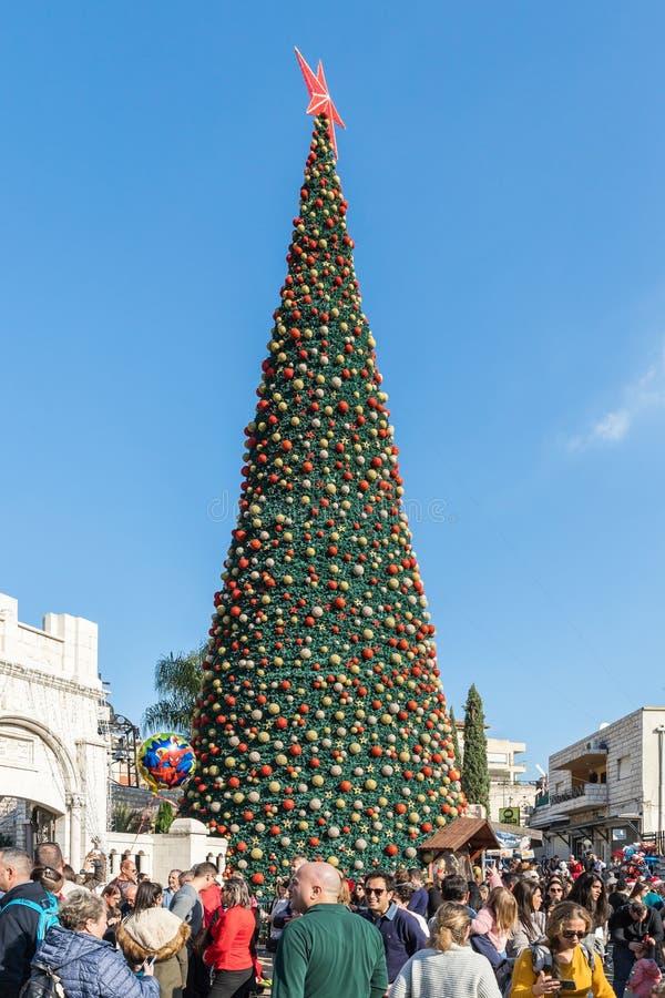 众多的游人在正方形附近走在圣诞树附近在拿撒勒市在以色列 免版税图库摄影