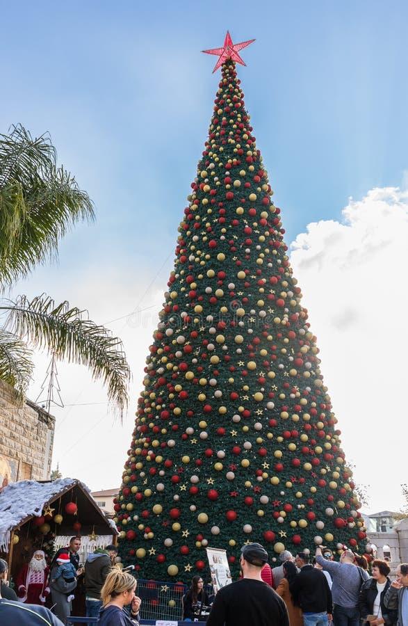 众多的游人在正方形附近走在圣诞树附近在拿撒勒市在以色列 免版税库存图片