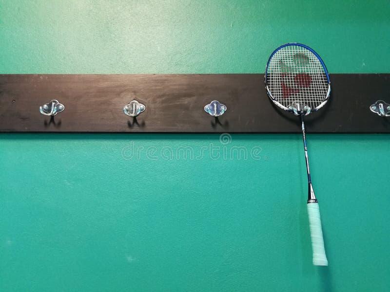 优乃克在绿色墙壁上的球拍吊在羽毛球健身房 免版税图库摄影