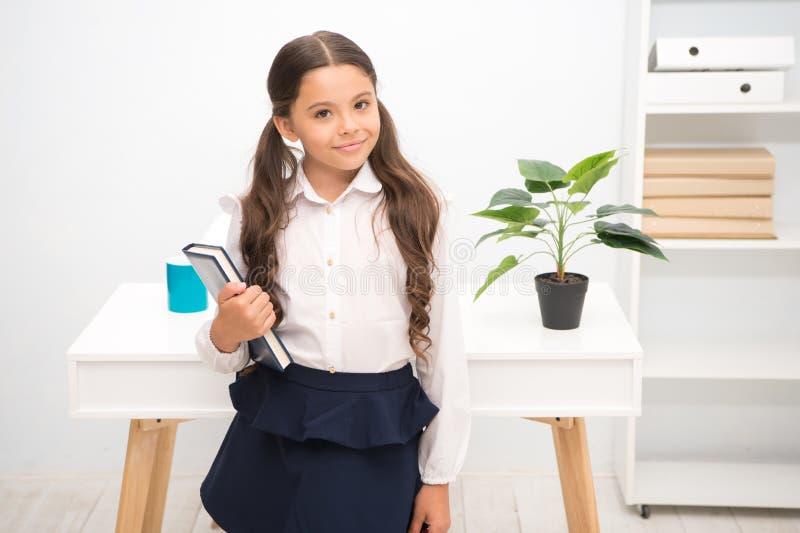 优秀第一前 女孩儿童举行书,当立场桌白色内部时 学习课本的女小学生 孩子学校 免版税图库摄影