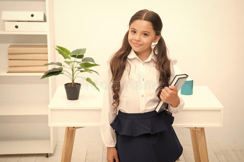 优秀第一前 女孩儿童举行书,当立场桌白色内部时 学习课本的女小学生 孩子学校 图库摄影
