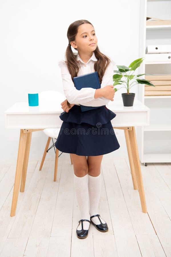 优秀第一前 女孩儿童举行书,当立场桌白色内部时 孩子校服愉快的面孔举行书 免版税库存照片