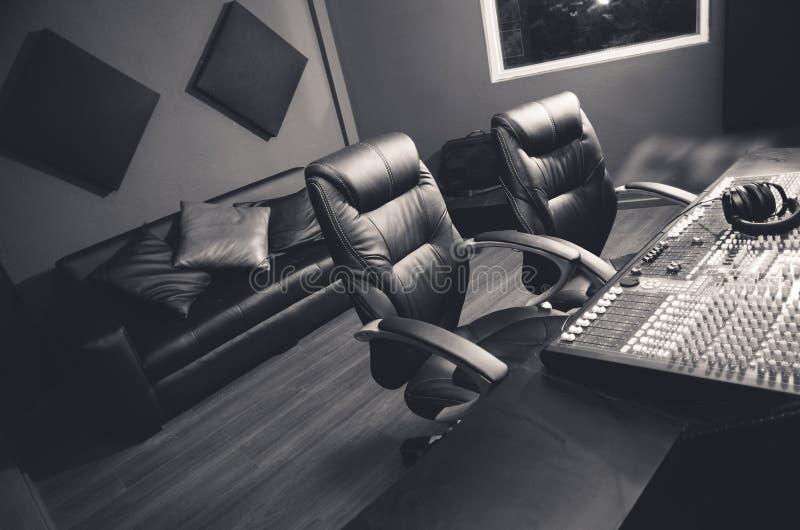 优等的专业录音室设定、大书桌有混合的控制台的和两把椅子,窗口声音摊的,沙发 免版税库存照片