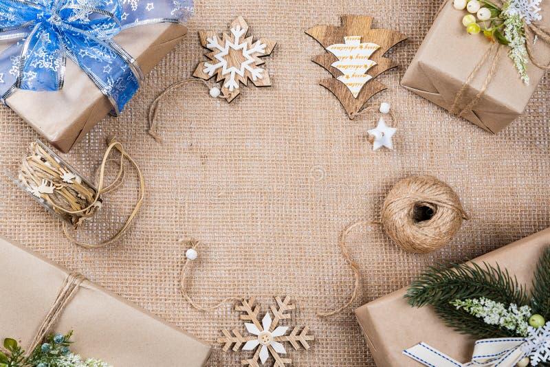 优等的圣诞节礼物盒在与玩具和新年装饰的包装纸提出在粗麻布 图库摄影