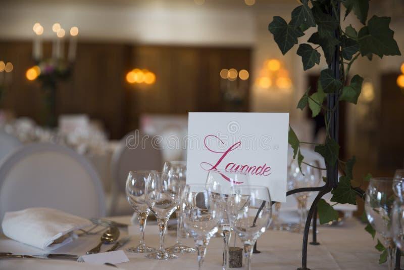 优美地服务与婚姻的玻璃,利器和用与白色桌布和灼烧的蜡烛的花桌装饰 免版税图库摄影
