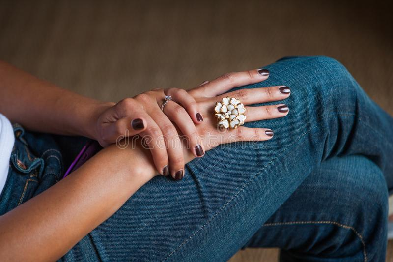 优美地pedicured夫人递与与一个花卉手被制作的豪华圆环的marroon黑暗的指甲油 库存照片