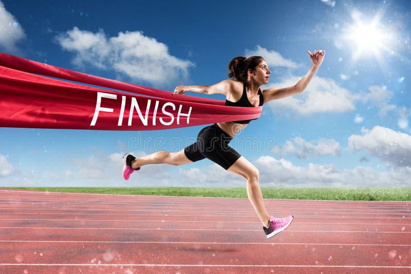 优胜者在终点线的妇女赛跑者