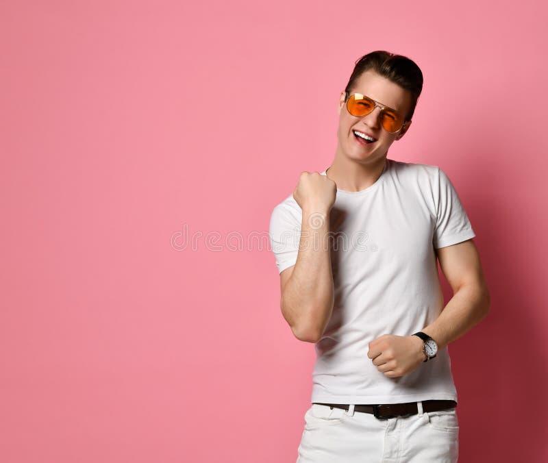优胜者庆祝 巨大成功 玻璃的快乐的年轻人与在桃红色演播室背景的一个愉快的表情 免版税库存图片