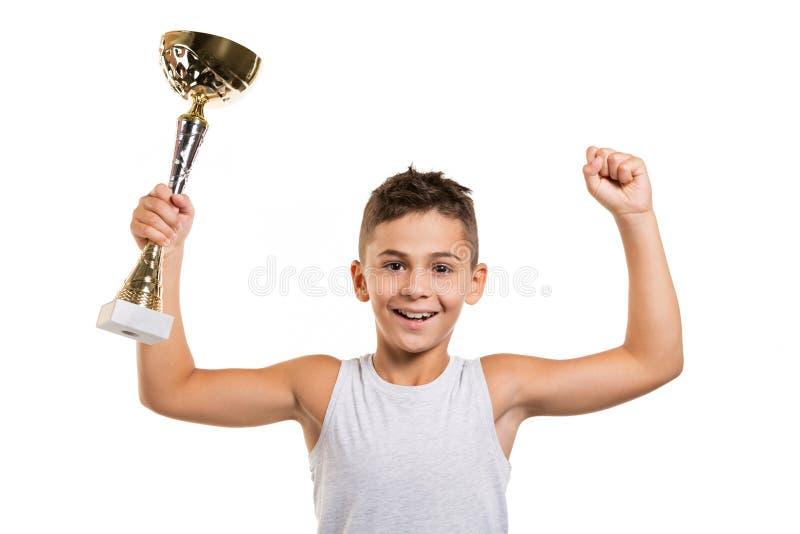 优胜者或领导概念,有体育杯子的男孩在他的手上,培养了他的手和微笑,胜利喜悦,在白色背景 库存图片