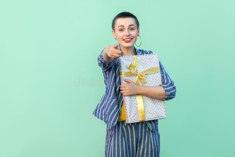 优胜者是您!画象愉快美丽与镶边衣服身分的短发年轻女人,拥抱当前箱子和指向 库存图片