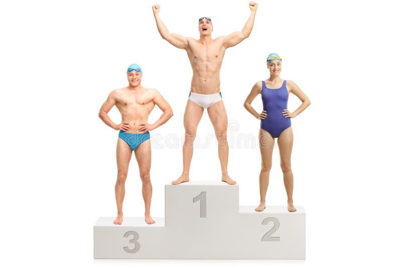 优胜者` s垫座的三位游泳者庆祝胜利的 库存图片