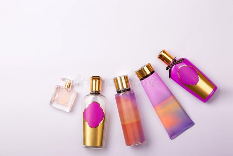 优质皮肤护理化妆用品和香水在紫色背景 图库摄影
