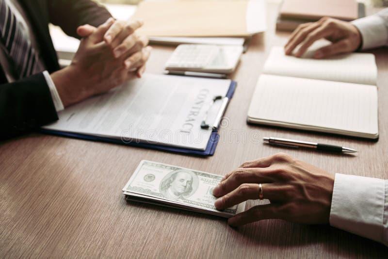 伙伴做了在销售合同和递了现金和笔的欺骗对签合同的商人 库存照片