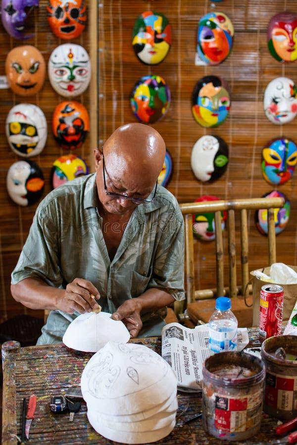 会安市,越南- 2019年6月:人绘画传统越南面具在他的车间 免版税库存图片