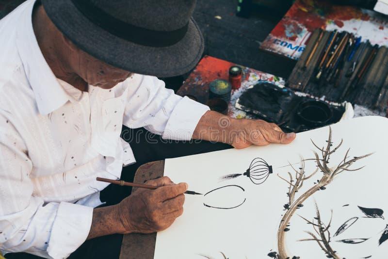 会安市,越南- 2019年6月:街道艺术家绘画传统灯笼 图库摄影