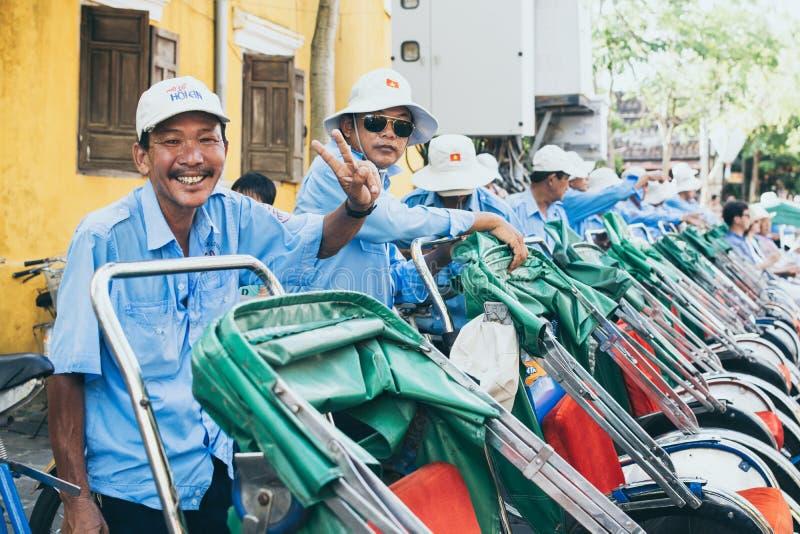 会安市,越南- 2019年6月:越南人力车微笑并且显示胜利标志用他的手 库存照片