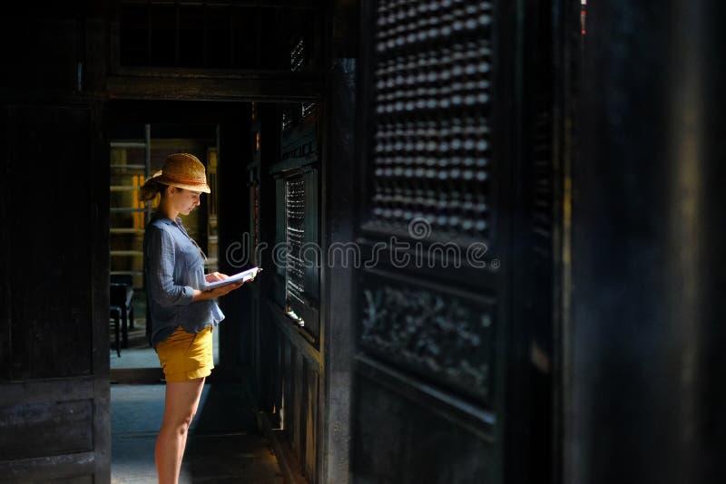 会安市/越南,11/11/2017:在一个传统房子Tan Ky的黑暗的木内部的女性旅游身分在会安市, 库存照片