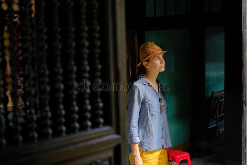 会安市/越南,11/11/2017:在一个传统房子Tan Ky的黑暗的木内部的女性旅游身分在会安市, 免版税库存照片