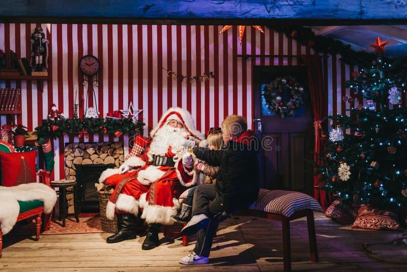 会见圣诞老人的孩子在冬天妙境圣诞节市场,伦敦,英国 免版税库存照片