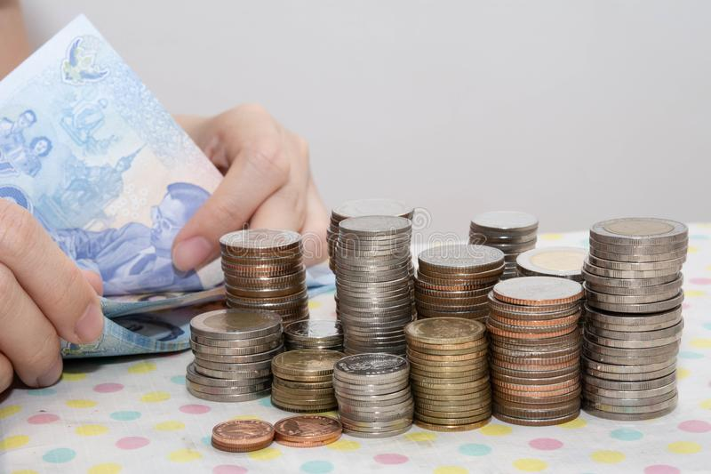 会计概念由计数在金钱硬币堆后的女性手提出泰铢票据在白色 免版税库存照片