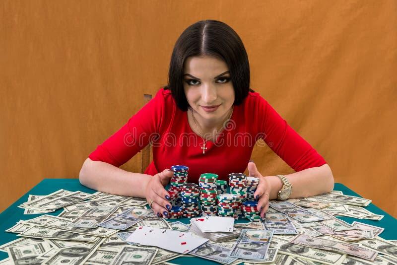 会集堆赌博娱乐场芯片的俏丽的妇女 库存图片