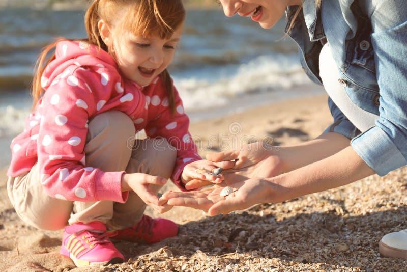 会集壳的母亲和小女儿在河附近 库存图片