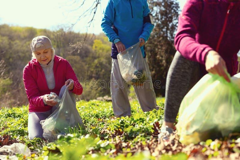 会集废弃物的快乐的志愿者在森林里 免版税库存图片