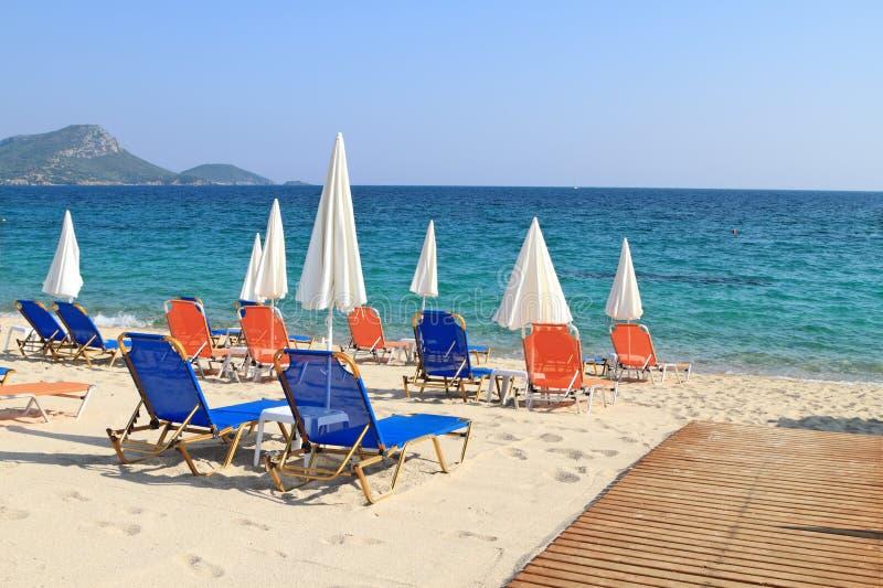 伞和可躺式椅由海 免版税库存图片