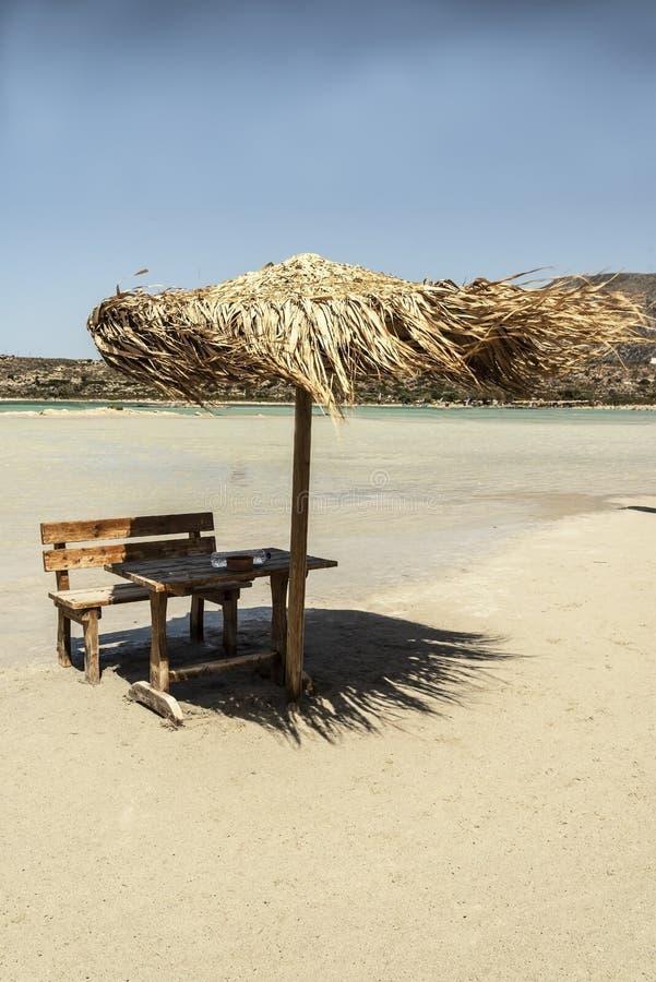 伞和木桌以希腊海为背景 免版税库存照片