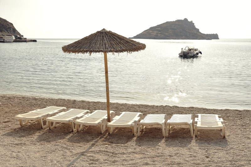 伞和空的sunbeds在沙滩在假期时 库存照片