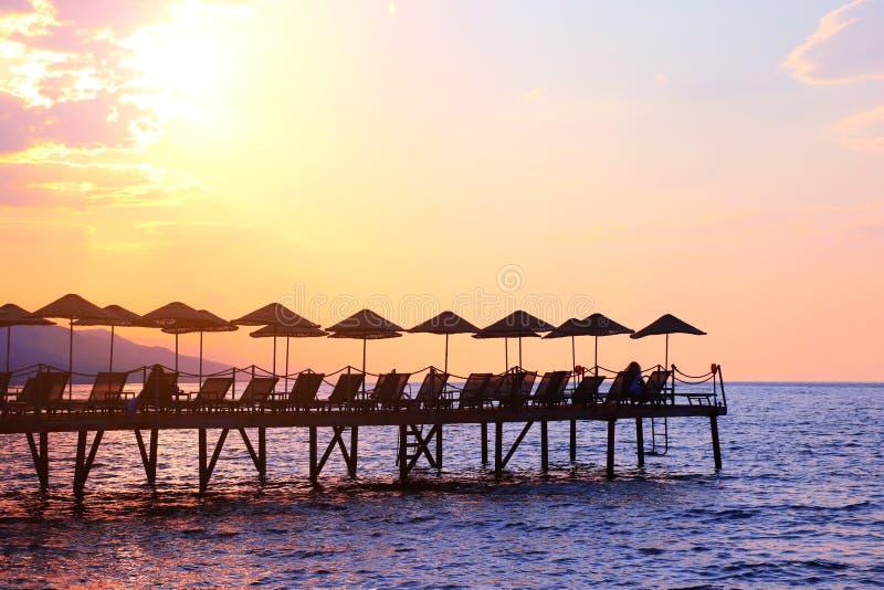伞和轻便折叠躺椅剪影在日落天空背景,土耳其 库存图片