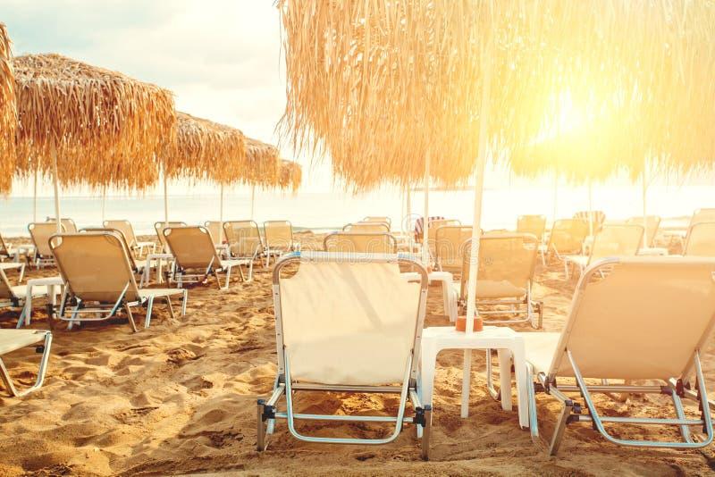 伞和sunbeds在海滩线背景 在海洋海滩的假期,夏天休假概念 库存照片