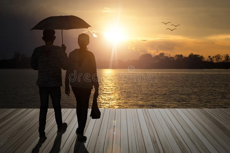 伞夫妇藏品给在木阳台的恋人步行,厕所 免版税库存图片