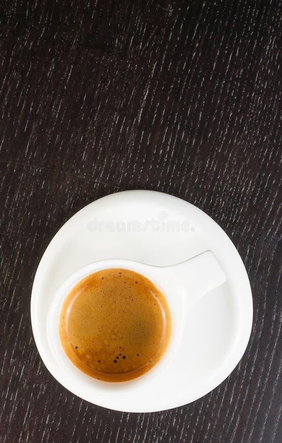 伟大的意大利咖啡看法上面在一个白色杯子的在黑木桌上 图库摄影